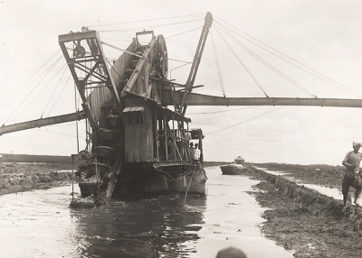 Une drague à vapeur sur un petit canal. Ses ailes sont des convoyeurs qui portent les sédiments de côté pour aider à créer une berge.